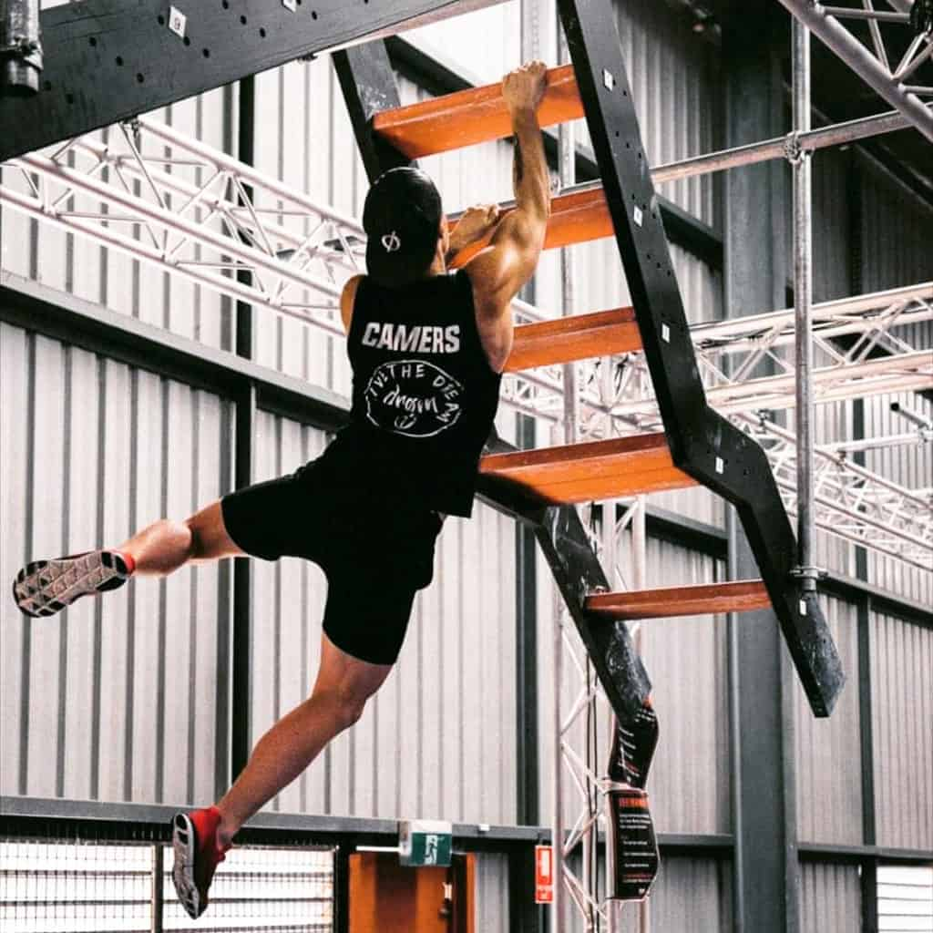 Cameron from Australian Warrior Fitness hanging from climbing stairs